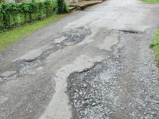 Picture show bad roads with potholes and uneven surface.