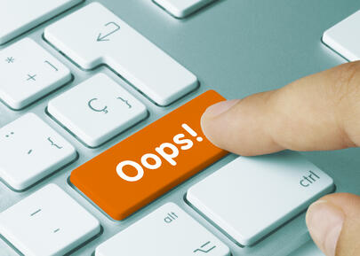 Picture of finger pressing the 'ooops' button on a computer to signify the human errors in fleet management