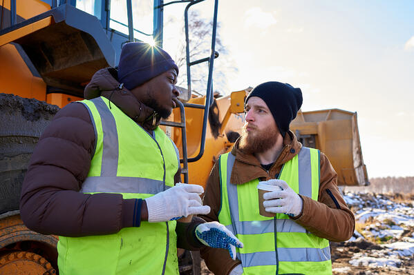 two-workers-next-to-idling-construction-vehicle-chatting-and-having-coffee